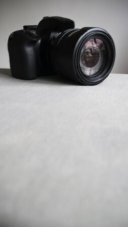 Black digital camera isolated on a light background
