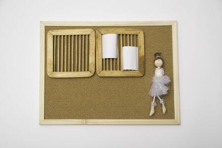 Weißer Memo-Stick und Ballerina-Puppe in Weiß auf leerem Korkbrett mit Korkbrett-Texturhintergrund mit Holzrahmen Standard-Bild