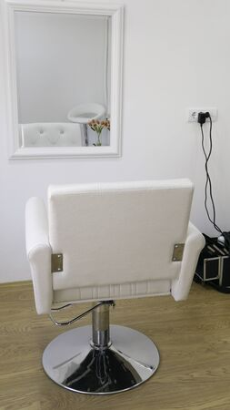 White hairdressing chair in front of the mirror