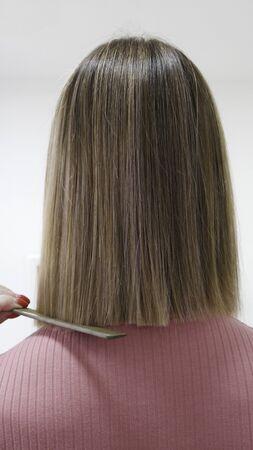 Peluquería peine el cabello de un modelo de mujer rubia Foto de archivo
