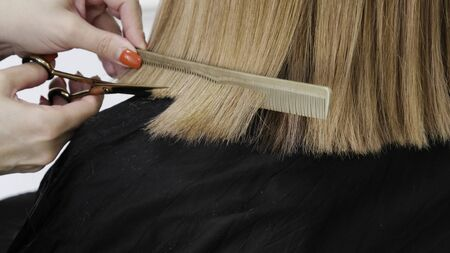 A close-up of hairdressers hands cutting red hair