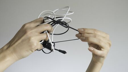 Black and white cables in a womans hand on isolated background 写真素材
