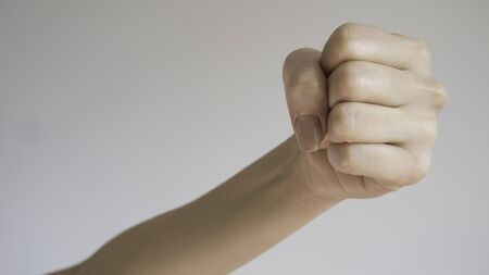 Woman's fist isolated on a light gray background.