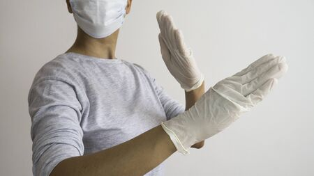 Woman with a white medical mask and latex glove in karate position.