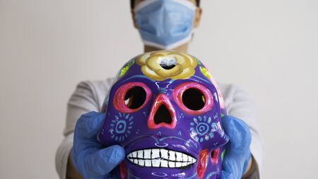 A woman with a surgical mask holding decorated colorful skulls. Day of dead, Mexico.