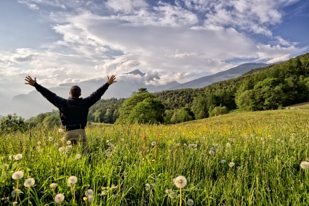 outstretched arms: One man with arms outstretched worshiping God in field, copy space
