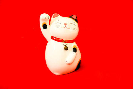 maneki: maneki neko lucky cat on red background