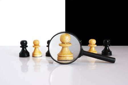 midst: White pawn enlarged with magnifier. Standing in a row with other black and white pawns. Stock Photo