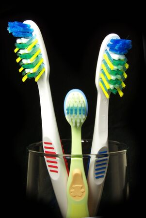 All  (three) tooth-brushes on the black background. photo