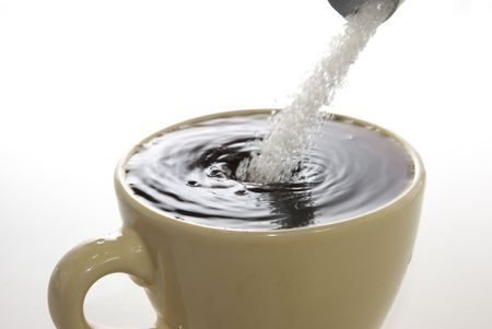 throw up: Dropping sugar into the coffee cup, white background, isolated.