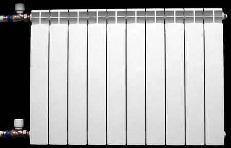 White aluminium radiator on the black background, installed into central heating system. Stok Fotoğraf