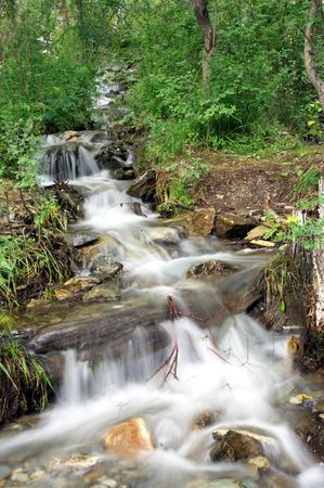 Cascades of the mountain river in the forest. photo