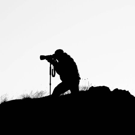 Silhouette of photographer on the hill with white background. Stock Photo