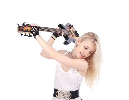 Young blond woman try to crash the electric bass guitar, isolated on the white background. photo