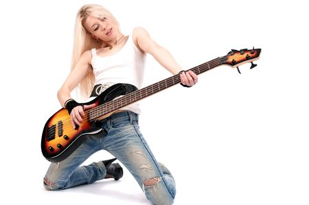 Young blond woman stay on knees and play on the guitar, isolated on the white background.