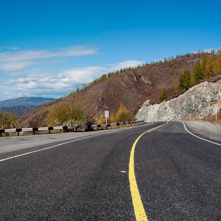 Empty mountain road with yellow marking photo