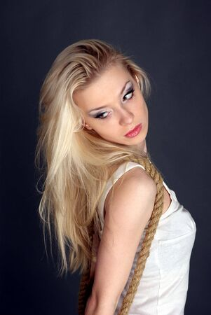 hair tied: Pretty young blond woman twisted with the rope Stock Photo
