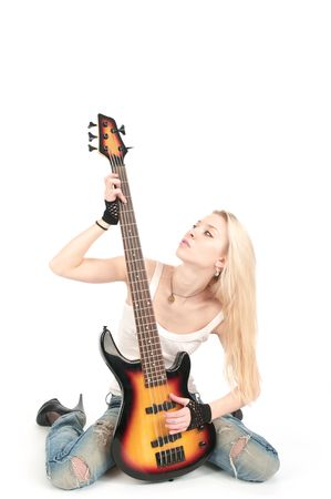 Young blond woman with rock guitar, isolated on the white background. photo