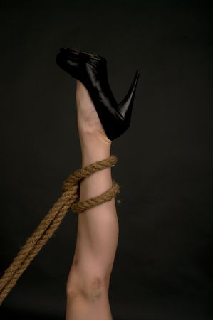 domination: Bound leg over black background Stock Photo