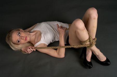tied woman: Cute young woman twisted with ropes