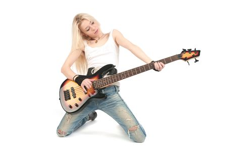 Young blond woman stay on knees and play on the guitar, isolated on the white background. photo