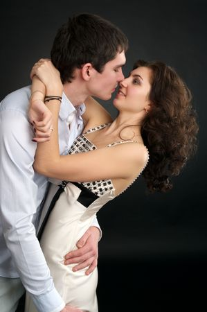 Portrait of embracing beautiful sexual couple over black photo