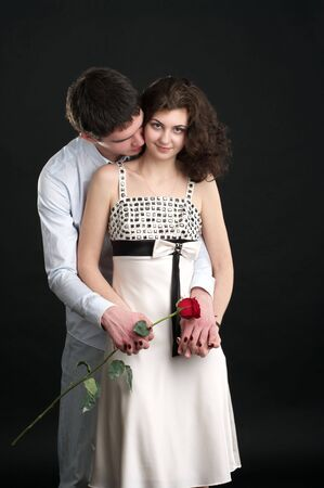 sexual couple: Portrait of beautiful sexual couple with red rose over black Stock Photo