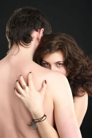 Beutiful sexual naked couple. Attractive woman looking over man shoulder.