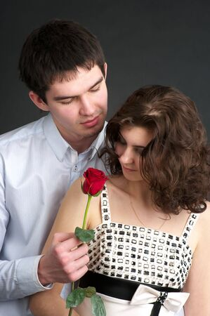 sexual couple: Portrait of cute sexual couple with red rose over black