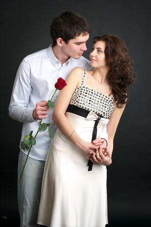 sexy couple black background: Portrait of beautiful sexual couple with red rose over black Stock Photo