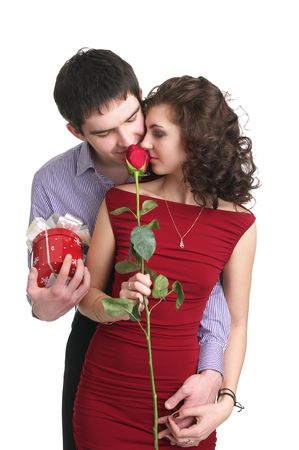 Attractive young couple with a gift and rose in hands isolated on the white background Stock Photo