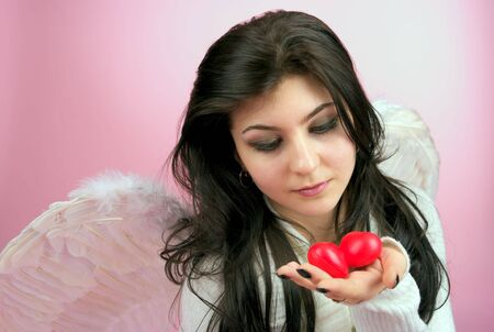 White angel girl with two red small hearts in the hand photo