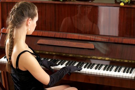 Young beautiful female performer in evening dress playing piano