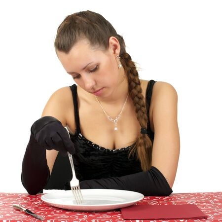 Beautiful girl sitting in restaurant with an empty white plate photo