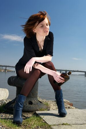 Lonely beautiful young woman sitting on pier with a wiskey bottle, feeling very sad. photo