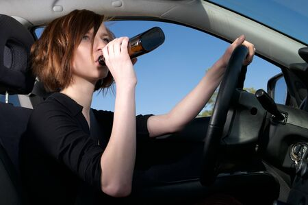 drink and drive: Depressed female driver drinking wiskey from a bottle Stock Photo