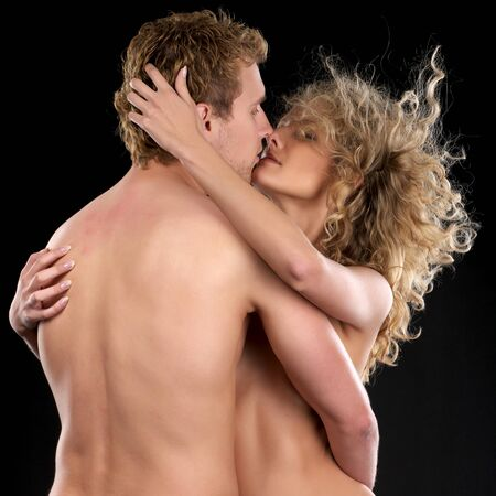 Beautiful naked couple in passion love over black background