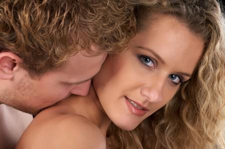Closeup portrait of beautiful naked couple. He kiss her neck. photo