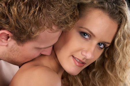 Closeup portrait of beautiful naked couple. He kiss her neck.