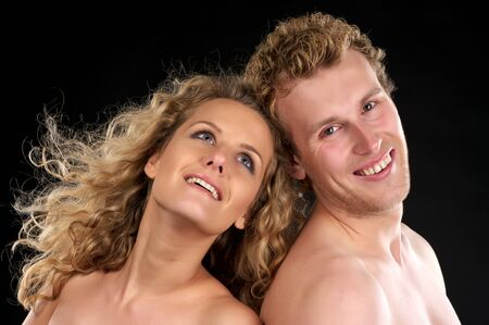 Closeup portrait of happy bautiful naked couple with curly hair over black background photo