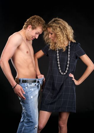 Beautiful young couple. She finds something interesting in his jeans.