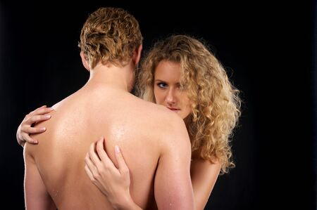 Beautiful naked couple with curly hair over black background photo