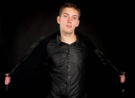 Handsome man takes off his (open) jacket over black background  photo
