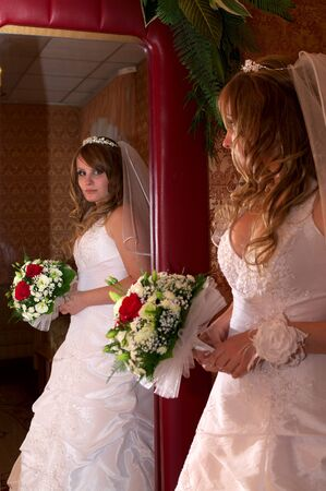 Beautiful bride with a wedding bouquet with reflection in a mirror  photo