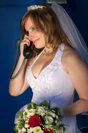 Happy bride talking on the blue public phone photo