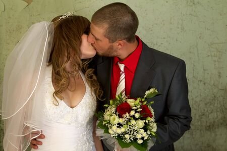 Bride and groom kissing in the old abandoned room photo