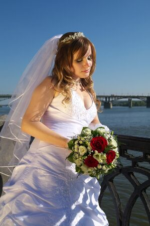 Bride with bouquet on the river quay photo