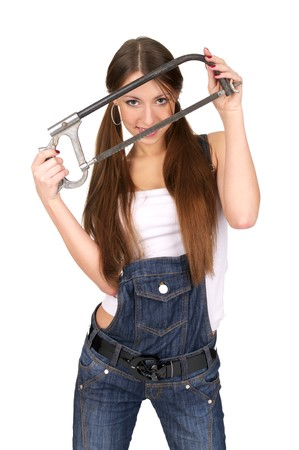 Attractive young woman in overalls holding handsaw, isolated over white background. photo