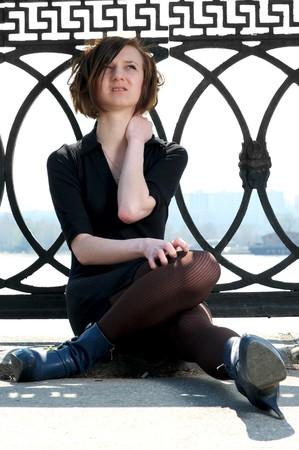 balustrade: Sad young female sitting near embankment balustrade