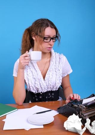 Cute female author with vintage typewriter writing something photo